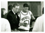 Coach Michael D. Theulen standing with Ivan Latimore in huddle (1995-1996)