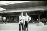 A photograph of two young men in front of Far Eastern building