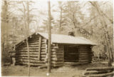 Log cabin with a man sitting on the roof